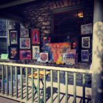 an outdoor gallery exhibition on the front porch of a stone house