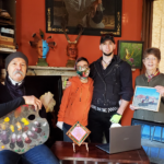 Adrian Martinez, Erin, Jerami, and Gwenn Knapp standing in front of the fireplace in Adrian's studio with some of our artwork.