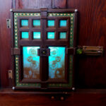 An illuminated panel attached by hinges to a wooden wall